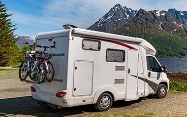 Husbil med cyklar parkerad i solen
