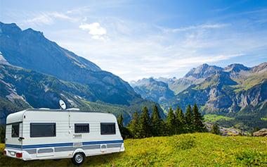 Vit och blå husvagn parkerad utomhus i naturen bland berg